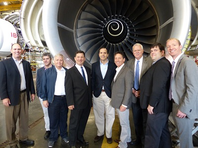 Ten people in front of jet engine under aircraft wing